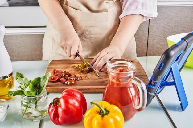 Teenager bereiten spaghetti bolognese aus einem online-lehrbuch zu und sehen sich digitale rezepte auf einem touchscreen-tablet an, während sie in der küche zu hause gesunde mahlzeiten zubereiten