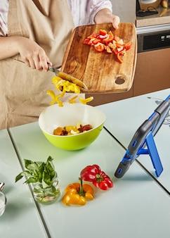 Teenager bereitet salat aus einem online-tutorial zu und sieht sich ein digitales rezept auf einem touch-tablet an, während er in der küche zu hause gesunde mahlzeiten zubereitet