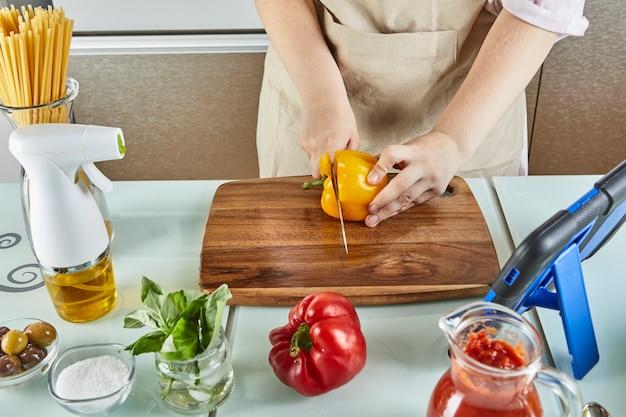 Teenager bereitet virtuelles online-seminar vor, schneidet gelben pfeffer, betrachtet digitale rezepte auf touchscreen-tablets, während er in der küche zu hause gesunde mahlzeiten zubereitet.