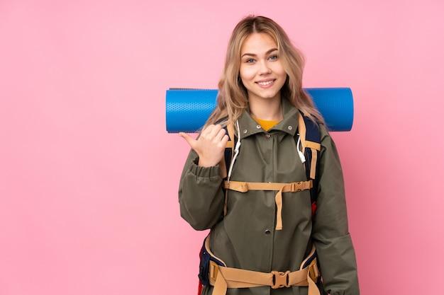 Teenager-bergsteiger-mädchen mit einem großen rucksack auf rosa, der zur seite zeigt, um ein produkt zu präsentieren