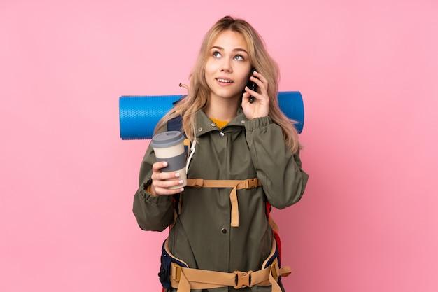 Teenager-bergsteiger-mädchen mit einem großen rucksack auf rosa wand, die kaffee zum mitnehmen und ein handy hält