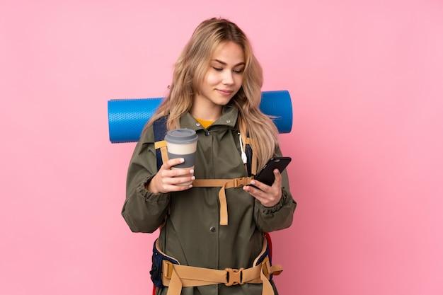 Teenager-bergsteiger-mädchen mit einem großen rucksack lokalisiert auf rosa wand, die kaffee zum mitnehmen und ein handy hält