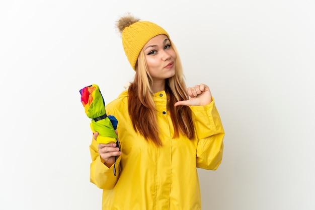 Teenager blondes mädchen trägt einen regenfesten mantel über isoliertem weißem hintergrund stolz und selbstzufrieden