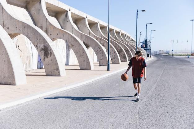 Teenager, der auf straße mit basketball geht