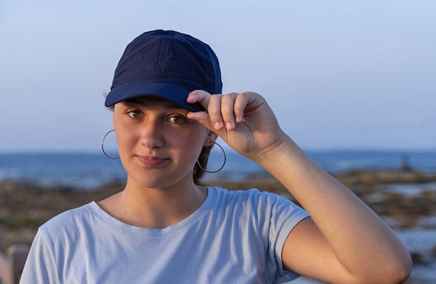 Teenager, der bei sonnenuntergang am meer steht und direkt in die kamera schaut. jugendlich mädchen, das t-shirt und dunkelblaue baseballmütze trägt und das visier berührt. modell von mütze und t-shirt