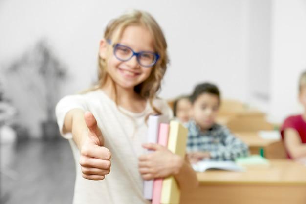 Teenager, der daumen oben im klassenzimmer in der schule zeigt.