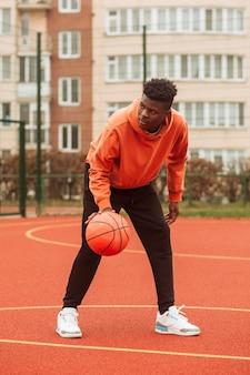 Teenager, der draußen basketball spielt