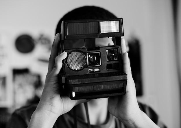 Teenager, der ein foto in einem schlafzimmerhobby- und -photographiekonzept macht