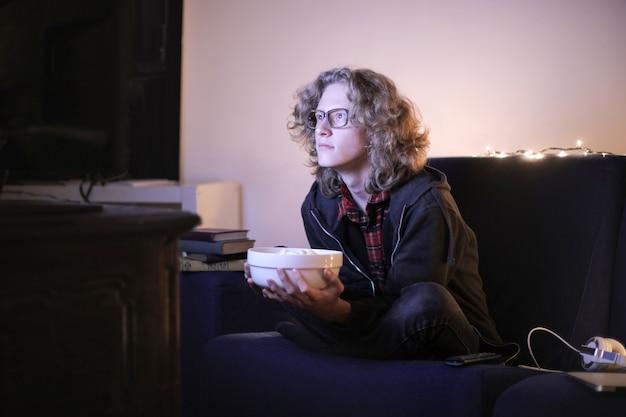 Teenager, der einen film alleine aufpasst