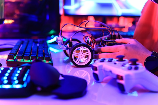 Teenager, der energie- und signalkabel zum sensorchip der spielzeugautowerkstatt einsteckt.