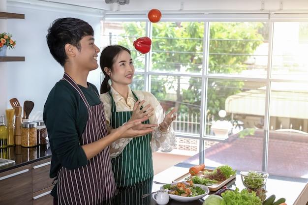 Teenager, der grünen pfeffer und tomaten betrachtet