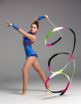 Teenager, der gymnastik macht, tanzt mit farbigem band auf grauem hintergrund
