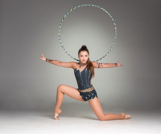 Teenager, der gymnastikübungen mit buntem reifen macht