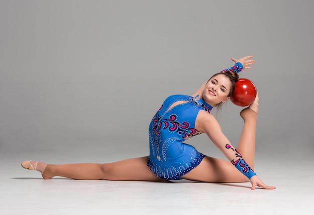 Teenager, der gymnastikübungen mit rotem gymnastikball macht