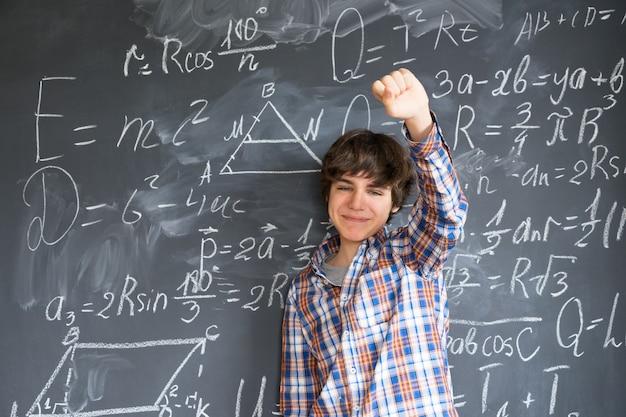 Teenager, der idee mit komplizierten mathematischen formeln auf tafel findet