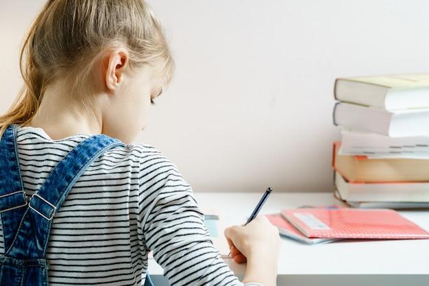 Teenager, der ihre hausaufgaben studiert und macht, während er stift mit kopienraum hält