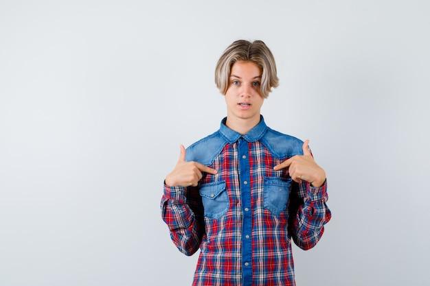 Teenager, der im karierten hemd auf sich selbst zeigt und unentschlossen aussieht, vorderansicht.