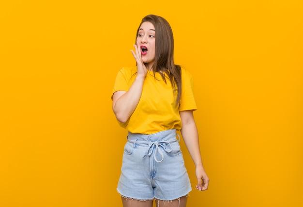 Teenager der jungen frau, die ein gelbes hemd trägt, sagt eine geheime heiße bremsnachricht und schaut zur seite