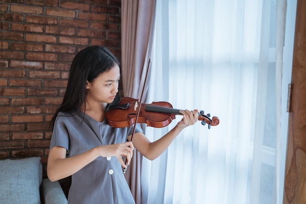 Teenager, der lernt, ein geigeninstrument zu spielen