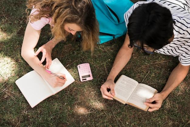 Teenager, der mit buch und notizblock auf gras liest