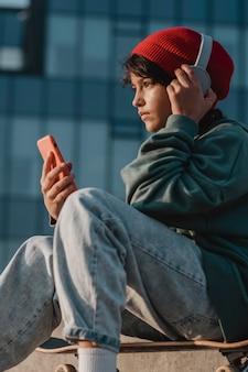 Teenager, der musik auf kopfhörern hört, während er smartphone benutzt