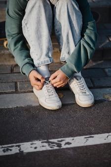 Teenager, der schnürsenkel im freien bindet