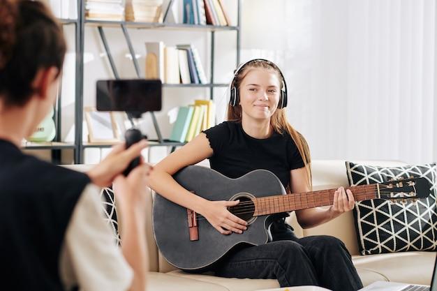 Teenager, der seine schwester filmt, die singt und gitarre für blog oder wettbewerb spielt