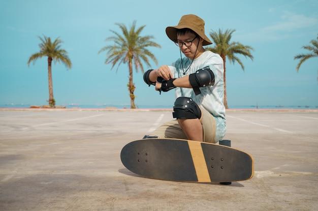 Teenager, der spaß mit skateboard hat und schutz in der stadt benutzt