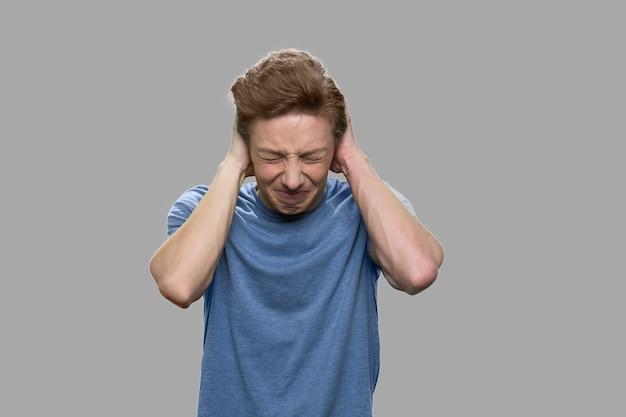 Teenager, der unter starken kopfschmerzen leidet. verzweifelter jugendlich junge auf grauem hintergrund schließen oben.