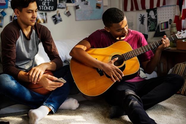Teenager, die heraus in einem schlafzimmer hängen, ein hobby- und musikkonzept der akustikgitarre spielend