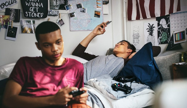 Teenager, die in einem schlafzimmer hängen, ein videospiel spielen und einen smartphone verwenden