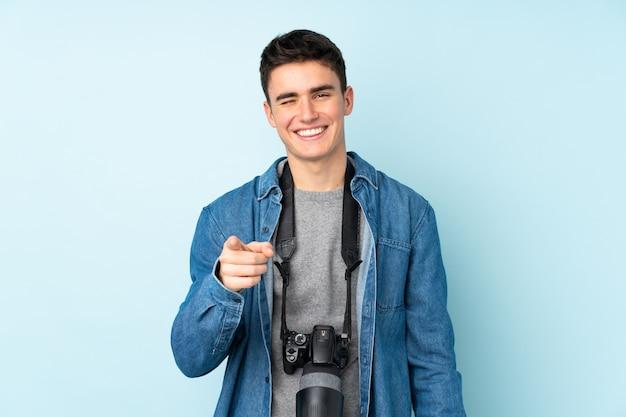 Teenager fotograf mann isoliert auf blaue wand zeigt finger auf sie