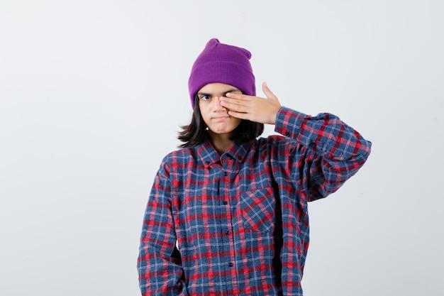 Teenager-frau, die das auge mit der hand in kariertem hemd und mütze bedeckt, sieht ernst aus