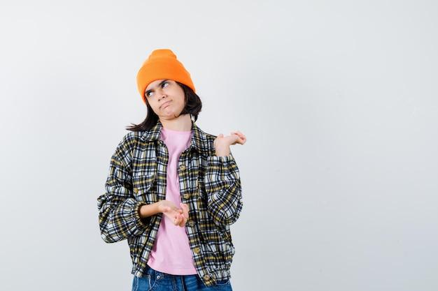Teenager-frau, die handflächen in t-shirt-jackenmütze ausbreitet, die verwirrt aussieht