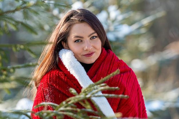Teenager-frau mit einem roten plaid auf seiner schulter im wald zwischen den schneebedeckten weihnachtsbäumen