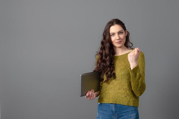 Teenager-frau mit langen gewellten haaren und tablette in den händen, lokalisiert auf einer grauen oberfläche