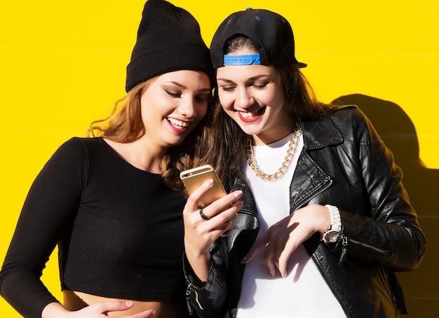 Teenager freundinnen im freien machen selfie an einem telefon.