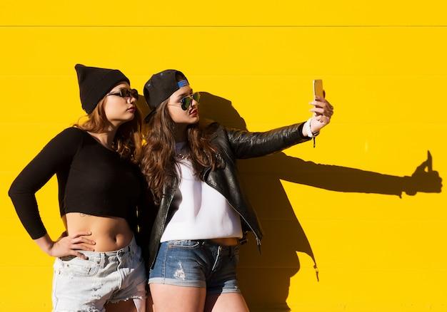 Teenager-freundinnen im freien machen selfie auf einem telefon.