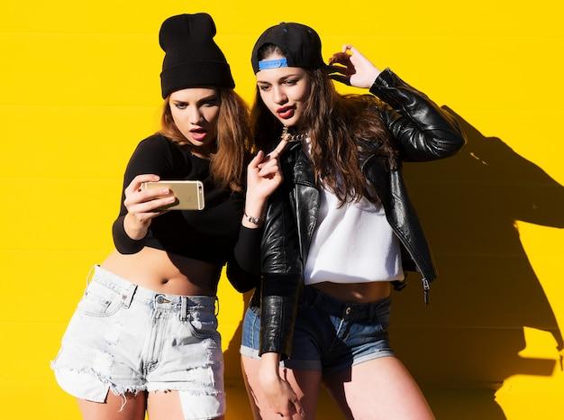 Teenager-freundinnen im freien nehmen selfie auf einem telefon.