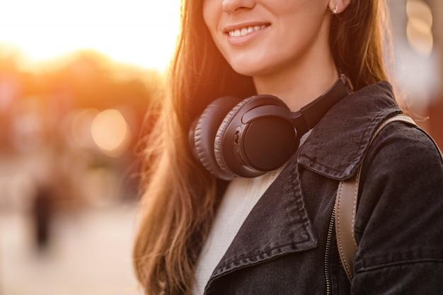 Teenager genießt und hört musik in schwarzen drahtlosen kopfhörern, während er durch die stadt geht