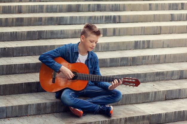 Teenager-gitarrenspiel, das auf den stufen im park sitzt.