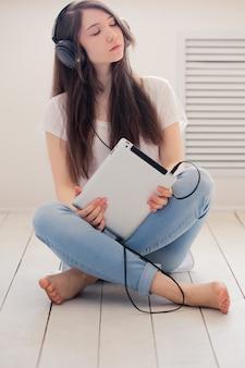 Teenager hört musik, die auf dem boden sitzt