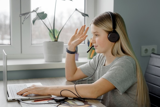 Teenager im kopfhörer hebt ihre hand, während sie online-unterricht zu hause hat