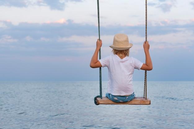 Teenager im strohhut auf see. rückansicht. seilschaukel über wasser. ruhig und entspannend.