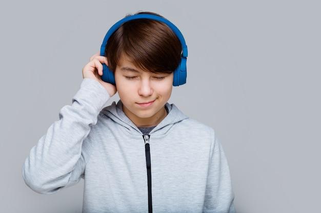 Teenager in blauen kopfhörern, die musik auf grau hören