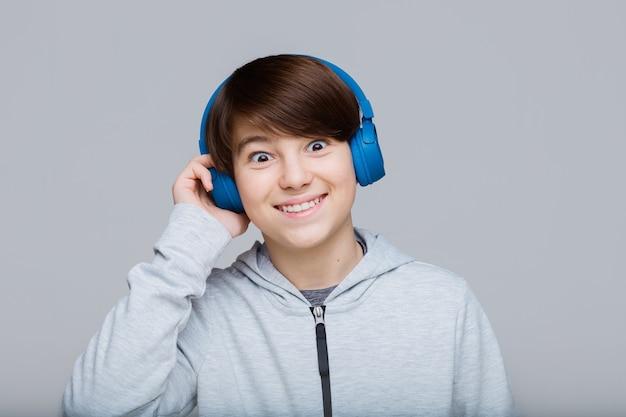 Teenager in blauen kopfhörern, die musik hören