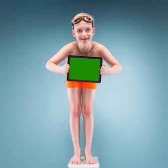 Teenager in den orange kurzen hosen und in den schwimmengläsern halten leere tablette
