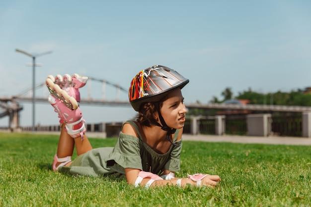 Teenager in einem helm lernt, auf rollschuhen im freien zu fahren