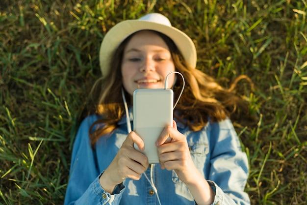 Teenager in hut mit kopfhörern liegt auf gras