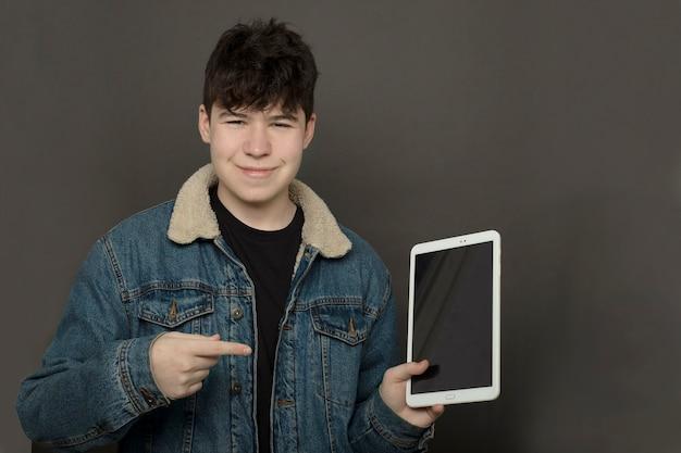 Teenager in jeansjacke, die auf tablettbildschirm zeigt
